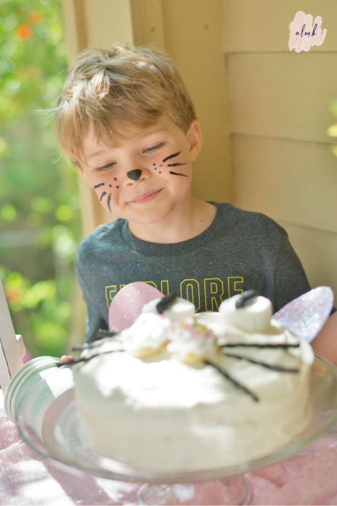 A friend checks out the homemade pretty kitty birthday cake. | ALMB
